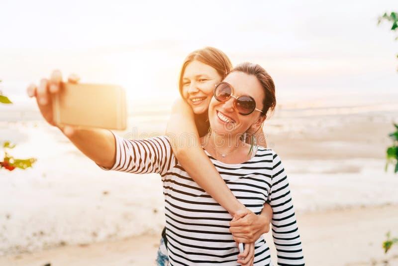 Dwa caucasian dziewczyny ściska i pozuje dla selfie na dennej stronie używa smartphone Niestaranny urlopowego czasu pojęcia wizer zdjęcia stock