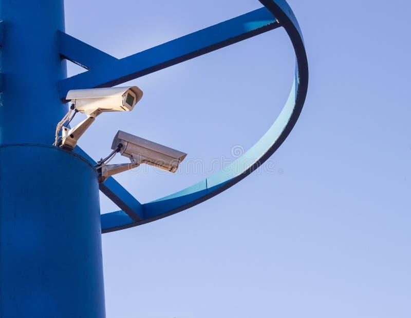 Dwa CCTV kamery na błękitnym filarze przeciw niebieskiego nieba tłu obraz stock