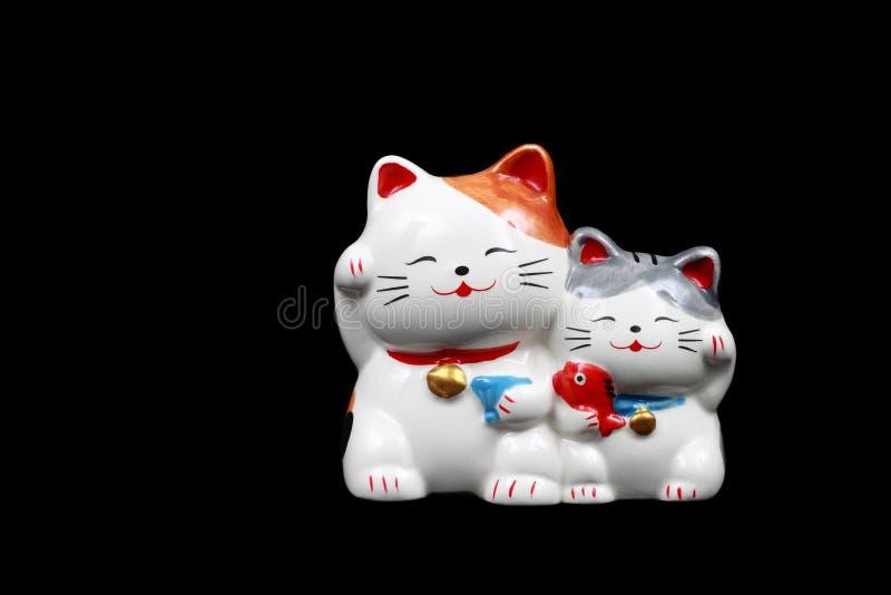 dwa ceramicznego szczęsliwego kota dla dekoraci odizolowywającej na czerni fotografia royalty free
