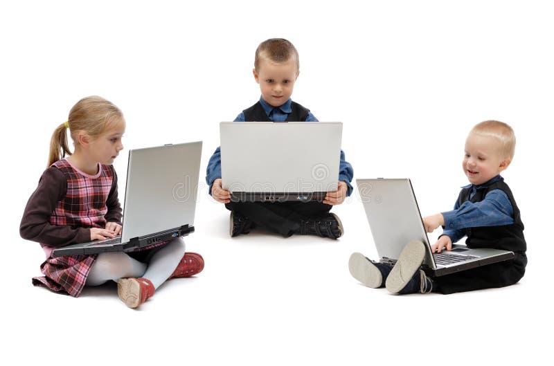 Dwa chłopiec i dziewczyna z laptopami obraz stock