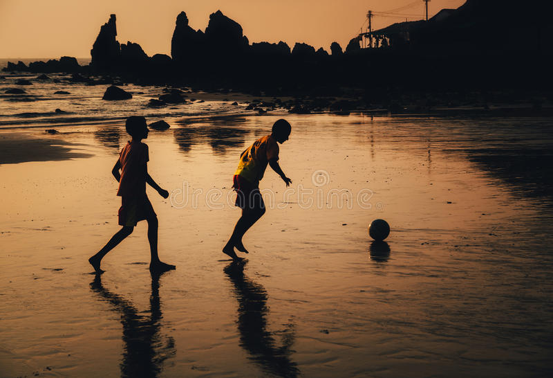Dwa chłopiec bawić się piłkę nożną na plaży w półmroku, Goa, India obrazy royalty free
