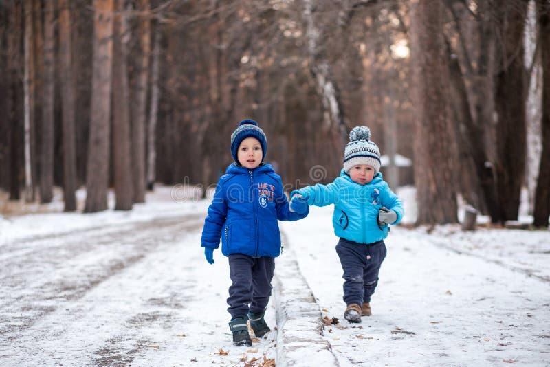 Dwa chłopiec bawić się w zima lesie fotografia stock
