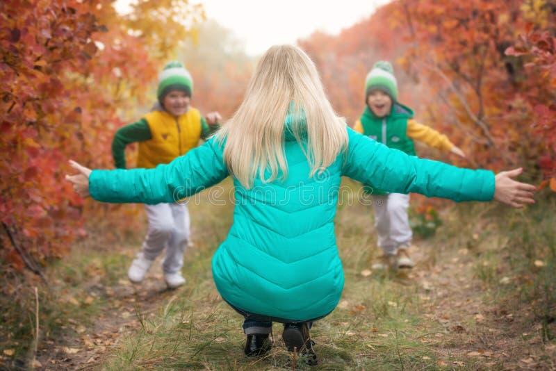 Dwa chłopiec bieg w kierunku jego matki w jesień słonecznym dniu, fotografia royalty free