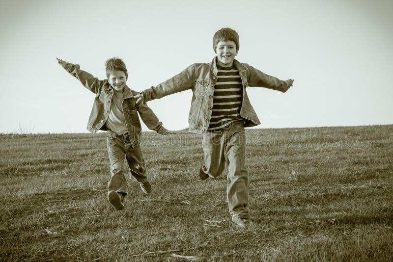 Dwa chłopiec biega wpólnie na łące, sepiowy stonowany zdjęcia stock