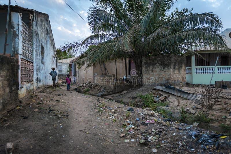Dwa chłopiec chodzi w brud ulicie wzdłuż otwartego kanału ściekowego przy Cupelon De Baixo sąsiedztwem w mieście Bissau zdjęcia stock