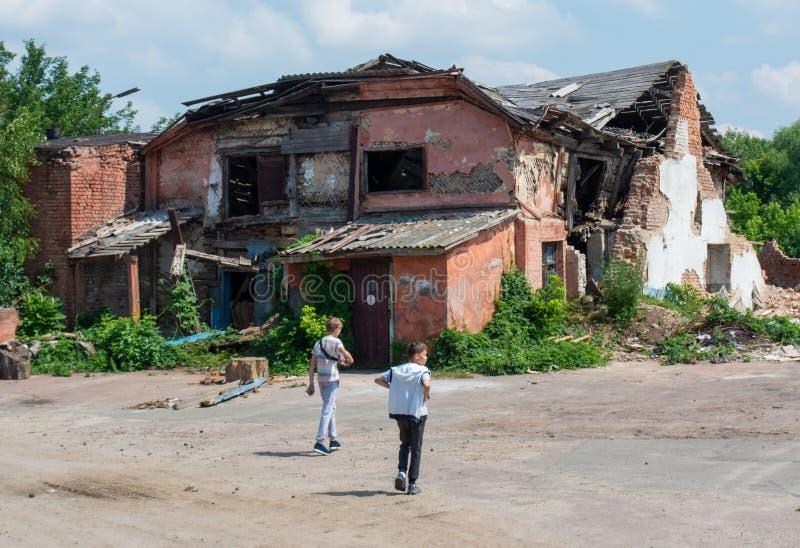 Dwa chłopiec chodzi w kierunku starego zaniechanego rujnującego strasznego domu zdjęcia stock