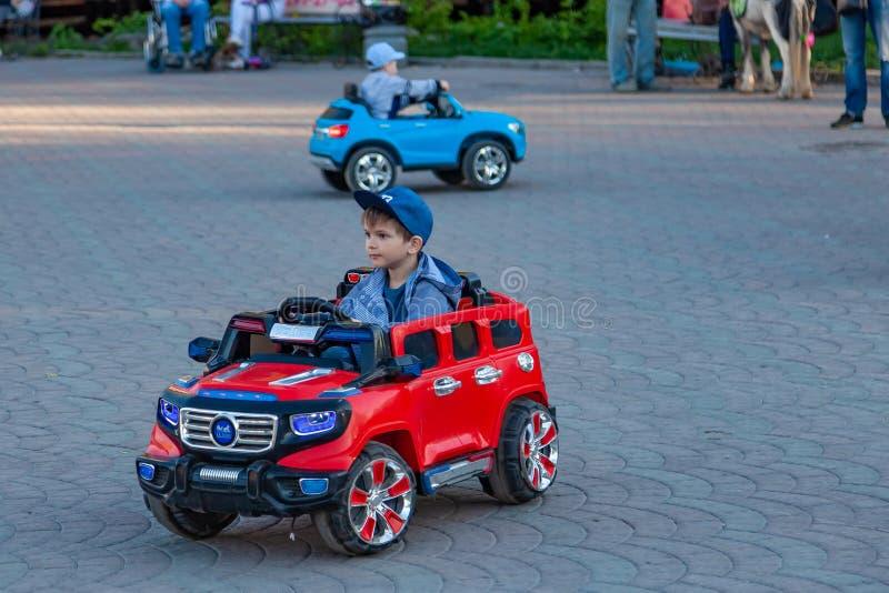 Dwa chłopiec jadą na czerwonych i błękitnych elektrycznych samochodach podczas gdy chodzący z ich rodzicami w miasto parku z ziel obraz royalty free