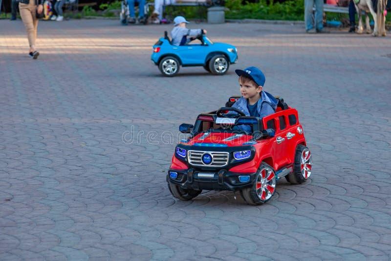 Dwa chłopiec jadą na czerwonych i błękitnych elektrycznych samochodach podczas gdy chodzący z ich rodzicami w miasto parku z ziel zdjęcie royalty free