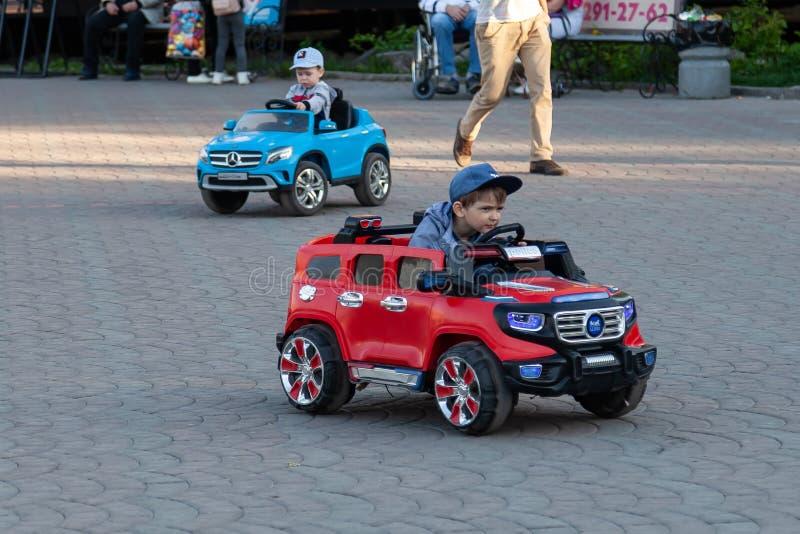 Dwa chłopiec jadą na czerwonych i błękitnych elektrycznych samochodach podczas gdy chodzący z ich rodzicami w miasto parku z ziel obrazy royalty free