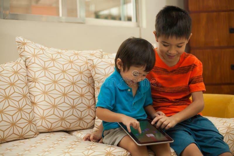Dwa chłopiec ma zabawę z cyfrową pastylką fotografia royalty free