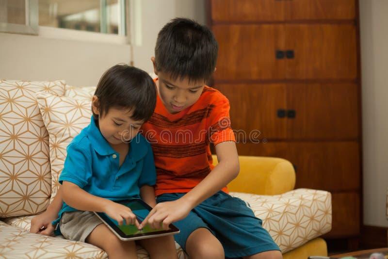 Dwa chłopiec ma zabawę z cyfrową pastylką obraz royalty free