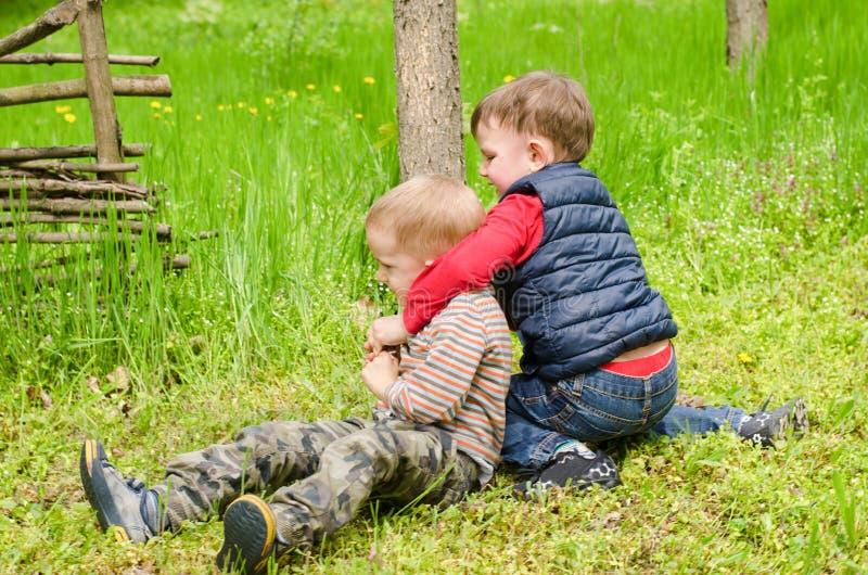Dwa chłopiec Mocuje się w trawie obraz royalty free