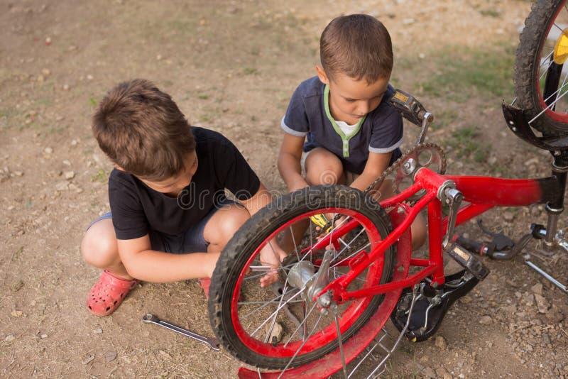 Dwa chłopiec naprawiają czerwonego rower outdoors, mień narzędzia, styl życia zdjęcia stock