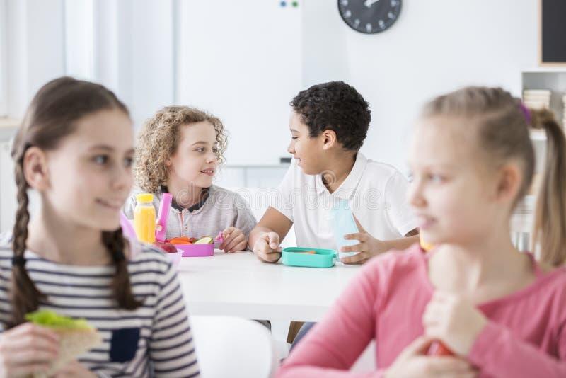 Dwa chłopiec opowiada podczas ich przerwa na lunch w a w tle zdjęcia royalty free
