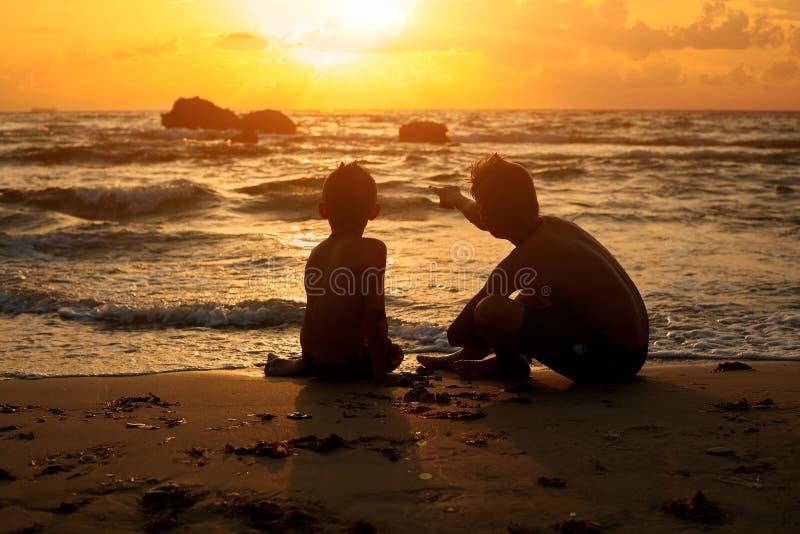 Dwa chłopiec siedzi na piasku patrzeje zmierzch cieszy się pięknego zmierzch po zabawa dnia na plaży fotografia stock