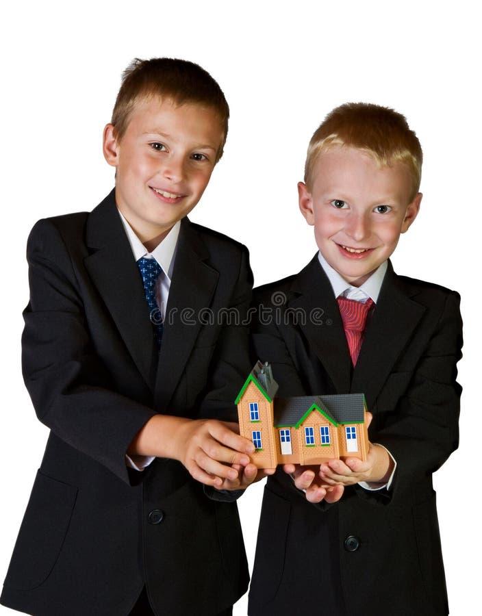 Dwa chłopiec target832_1_ zabawki dom, odosobnionego na biel fotografia royalty free