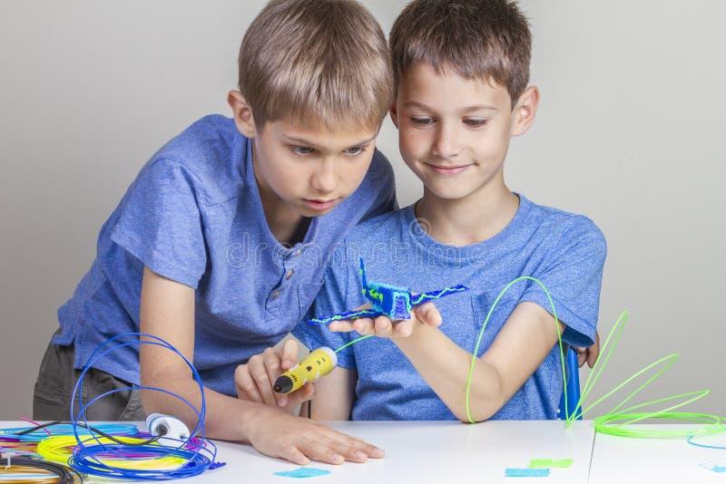 Dwa chłopiec tworzy z 3d druku piórami zdjęcie stock