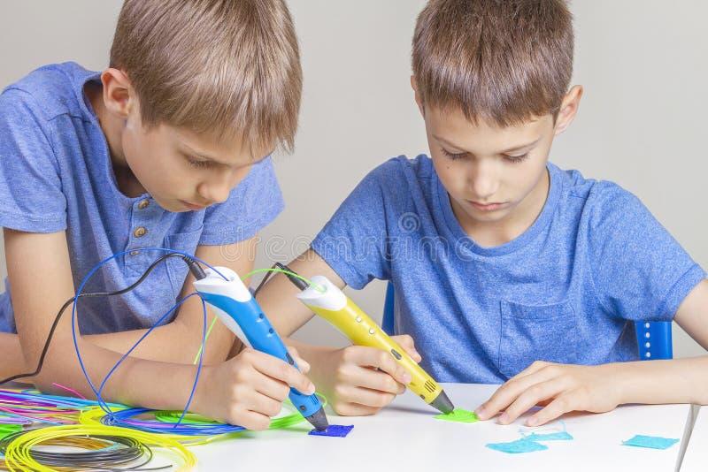 Dwa chłopiec tworzy z 3d druku piórami zdjęcie royalty free