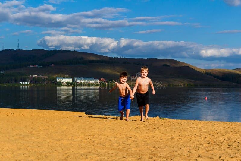 Dwa chłopiec w sportach zwierają bieg na żółtym piasku na plaży, mienie ręki zdjęcia stock