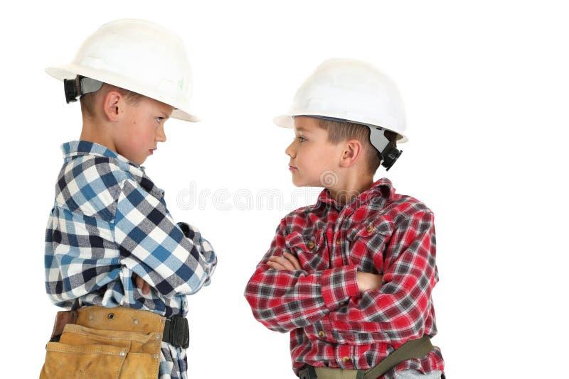 Dwa chłopiec walczy w budów hardhats zdjęcia royalty free