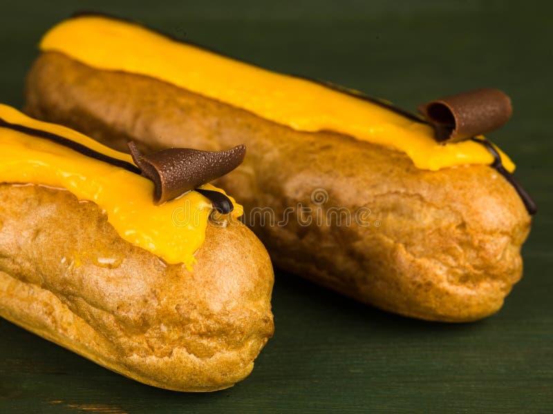 Dwa Choux ciasta pomarańcze Eclairs zdjęcia stock