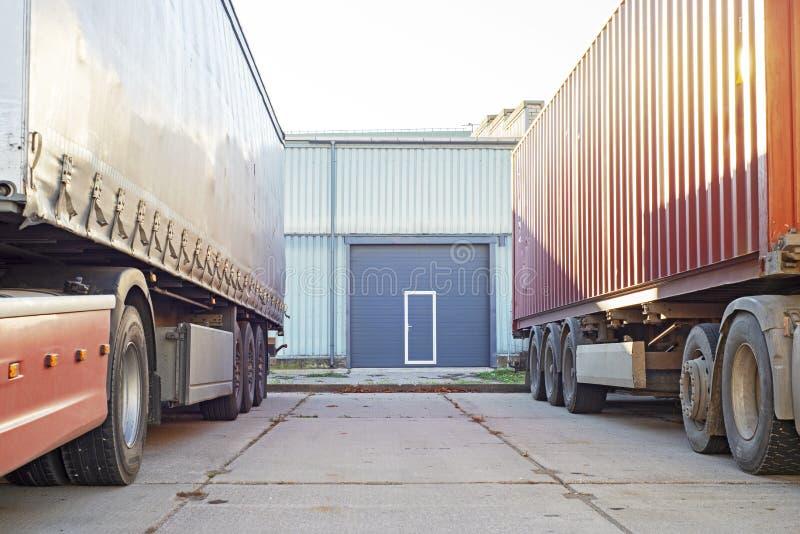 Dwa ciężarówki stoi blisko błękitnego garażu drzwi obrazy stock