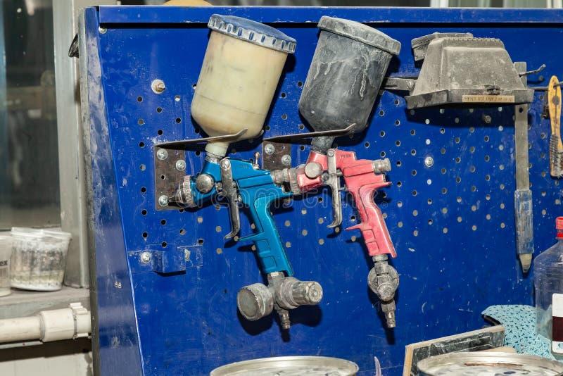 Dwa ciała farby pistoletu natryskowa czerwień i błękit instalujący na workbench w pojazdzie naprawiamy warsztat obok innej lampy  zdjęcia royalty free