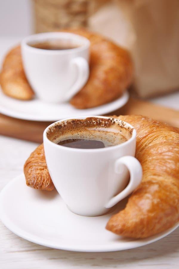 Dwa croissants obok one i filiżanki kawy zdjęcie royalty free