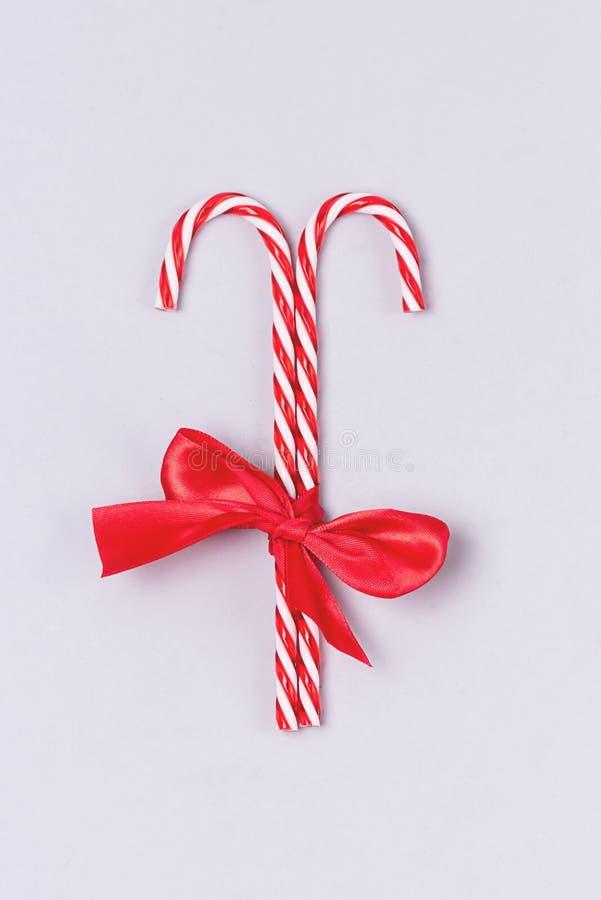 Dwa cukierki są połączone z czerwoną wstążką na jasnym tle świątecznego tła w pionie obrazy stock