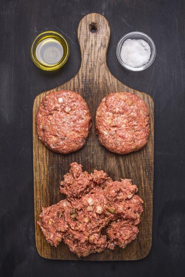 Dwa cutlets dla hamburgerów z minced mięsem na tnącej desce z ziele, masłem i solankowym drewnianym nieociosanym tło odgórnego wi fotografia stock