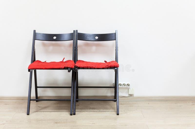 Dwa czarnego drewnianego krzesła z miękkimi poduszkami są blisko ściany zdjęcie royalty free