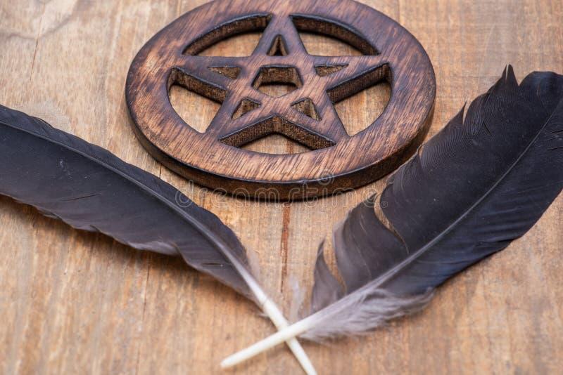 Dwa Czarnego kruka piórka i Drewnianego okrążonego pentagrama symbol na drewnie Pięć elementów: Ziemia, woda, powietrze, ogień, d zdjęcie royalty free