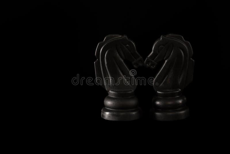 Dwa czarnego szachowego rycerza dotyka ich nosy na czarnym tle obraz stock