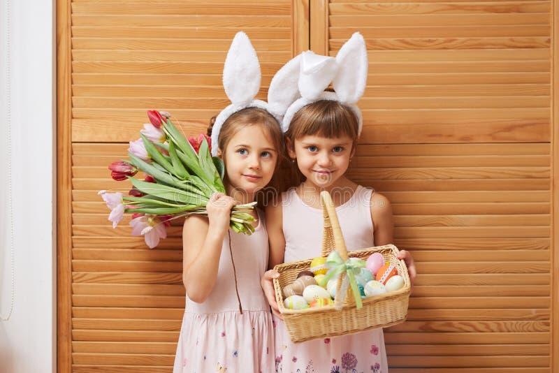 Dwa czarują małej siostry w sukniach z białymi królików ucho na ich głowa chwytach kwitną i kosz z obrazy royalty free