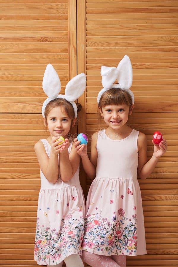 Dwa czarują małej siostry w sukniach z białymi królików ucho na ich głowach trzymają farbujących jajka w ich rękach na fotografia stock
