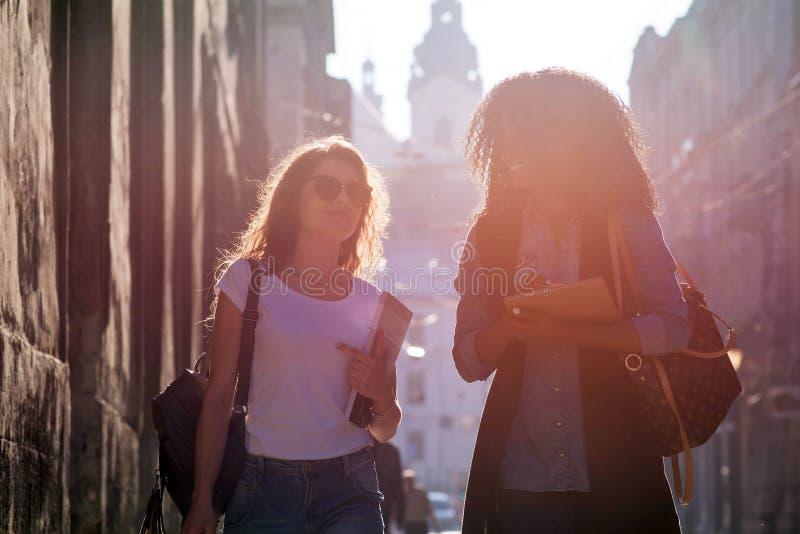 Dwa czarują mieszającego biegowego dziewczyna przyjaciela opowiadają podczas spaceru wzdłuż ulicy Zmierzchu pojęcie zdjęcia stock