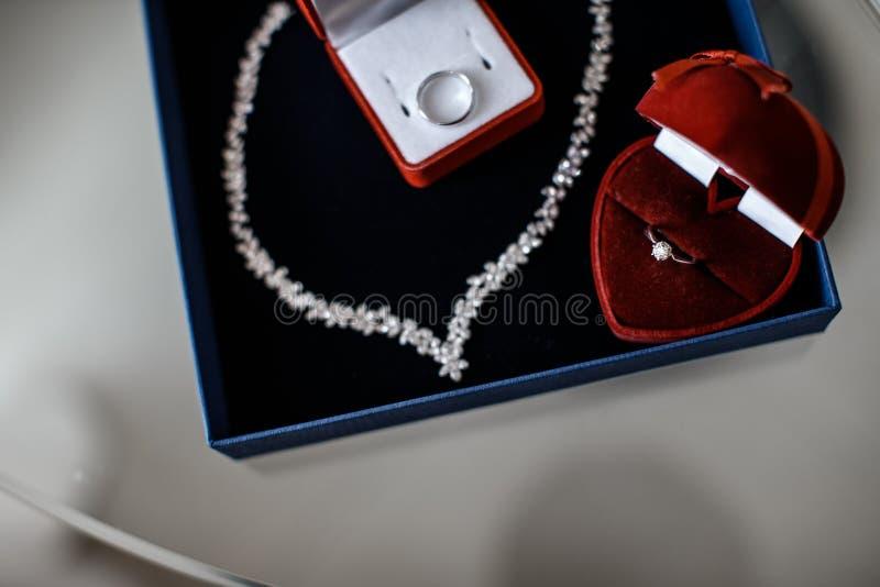 Dwa czerwieni ringowego pudełka z pierścionki w one i kolia blisko one kłamają wśrodku błękitnego biżuterii pudełka fotografia stock