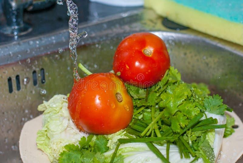 Dwa czerwonego świeżego pomidoru i zielonej pietruszka one czyścą wodnym spada puszkiem od zakładki zdjęcia stock