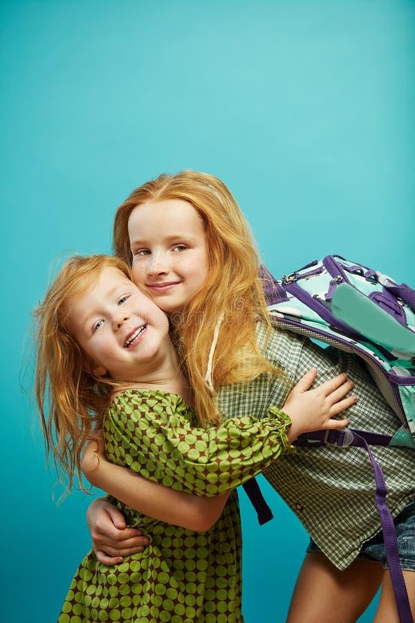 Dwa czerwonego z włosami dziecka siostrzany śliczny przytulenie odizolowywający na błękitnym tle obrazy stock