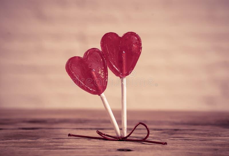 Dwa czerwony serce kształtował lizaki jako metafora miłość, więź i walentynka dzień, pojęcie zdjęcia royalty free