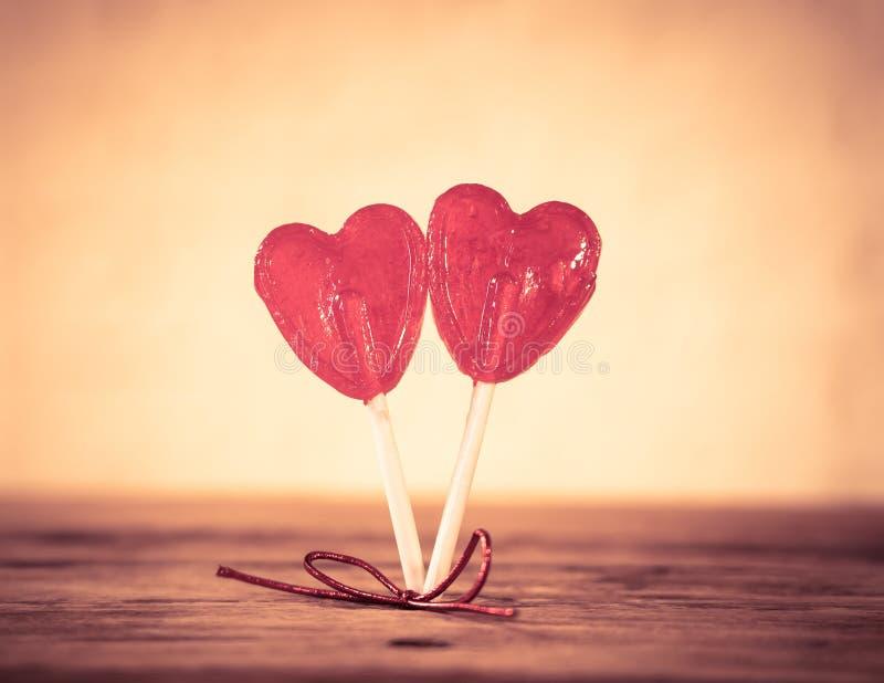 Dwa czerwony serce kształtował lizaki jako metafora miłość, więź i walentynka dzień, pojęcie zdjęcie stock