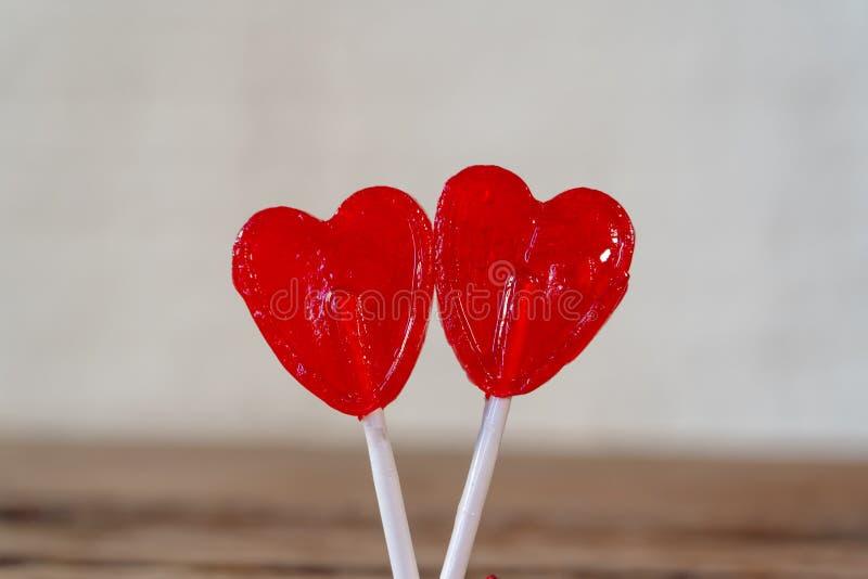 Dwa czerwony serce kształtował lizaki jako metafora miłość, więź i walentynka dzień, pojęcie fotografia royalty free