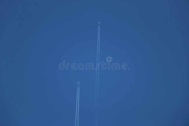 Dwa dżetowego samolotu latają w jasnym niebieskim niebie, opuszcza białego ślad dwa samolotu urlopu kondensaci śladu w jasnym nie obraz royalty free