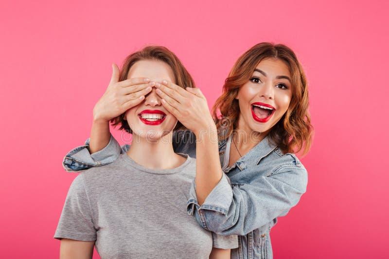 Dwa dama przyjaciela zakrywa oczy z rękami obrazy stock