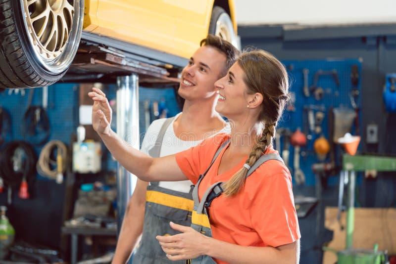 Dwa dedykowali auto mechaników sprawdza zmodyfikowanych koła nastrajający samochód obrazy stock