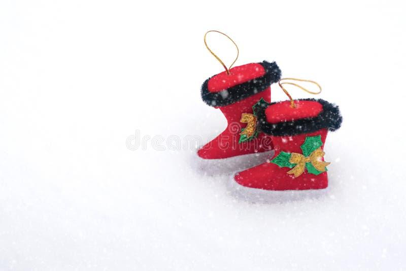 Dwa dekoracyjnego boże narodzenie buta na śnieżnym białym tle Bożenarodzeniowy wakacyjny tło z Santa butami, kopii przestrzeń obraz stock