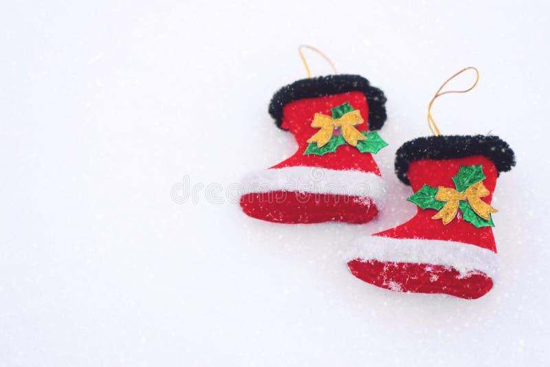 Dwa dekoracyjnego boże narodzenie buta na śnieżnym białym tle Bożenarodzeniowy wakacyjny tło z Santa butami, kopii przestrzeń zdjęcia stock