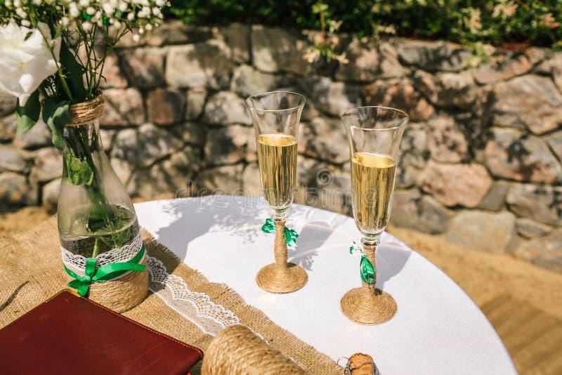 Dwa dekorowali szkła szampan na stole w jardzie przy ślubną ceremonią zdjęcia royalty free