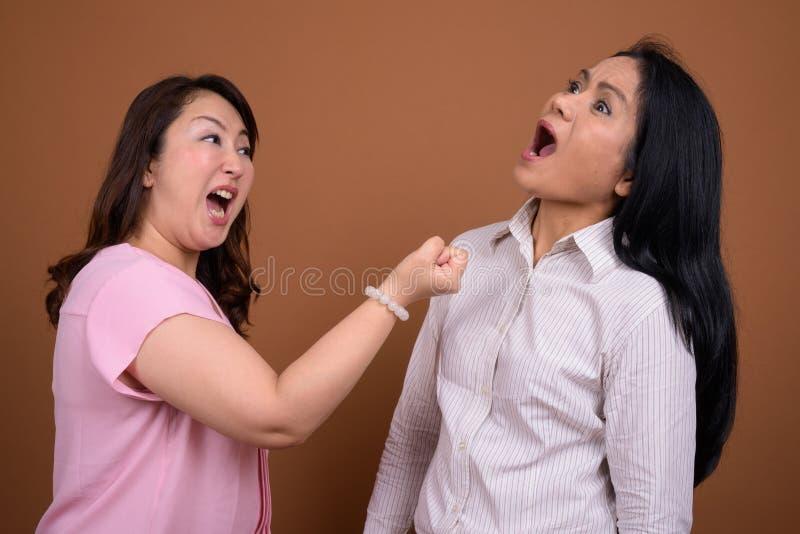 Dwa dojrzałego Azjatyckiego bizneswomanu wpólnie przeciw brown tłu zdjęcia royalty free