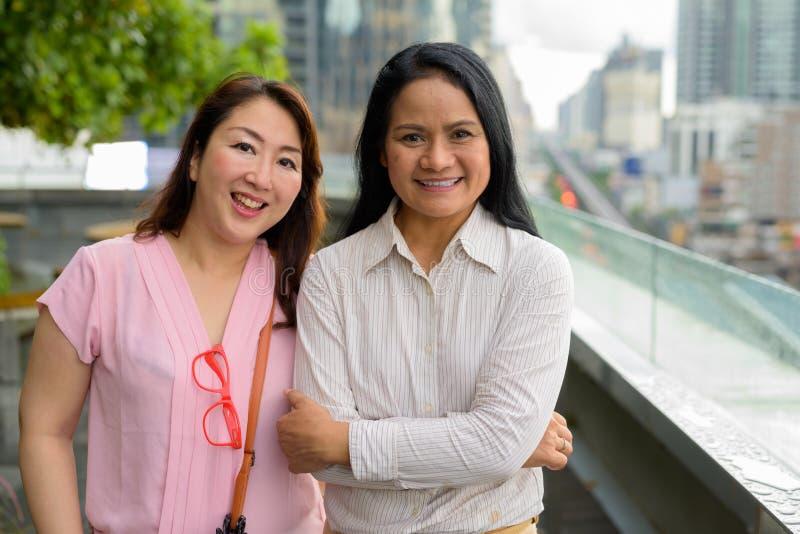 Dwa dojrzałej Azjatyckiej kobiety wpólnie przeciw widokowi miasto obrazy royalty free